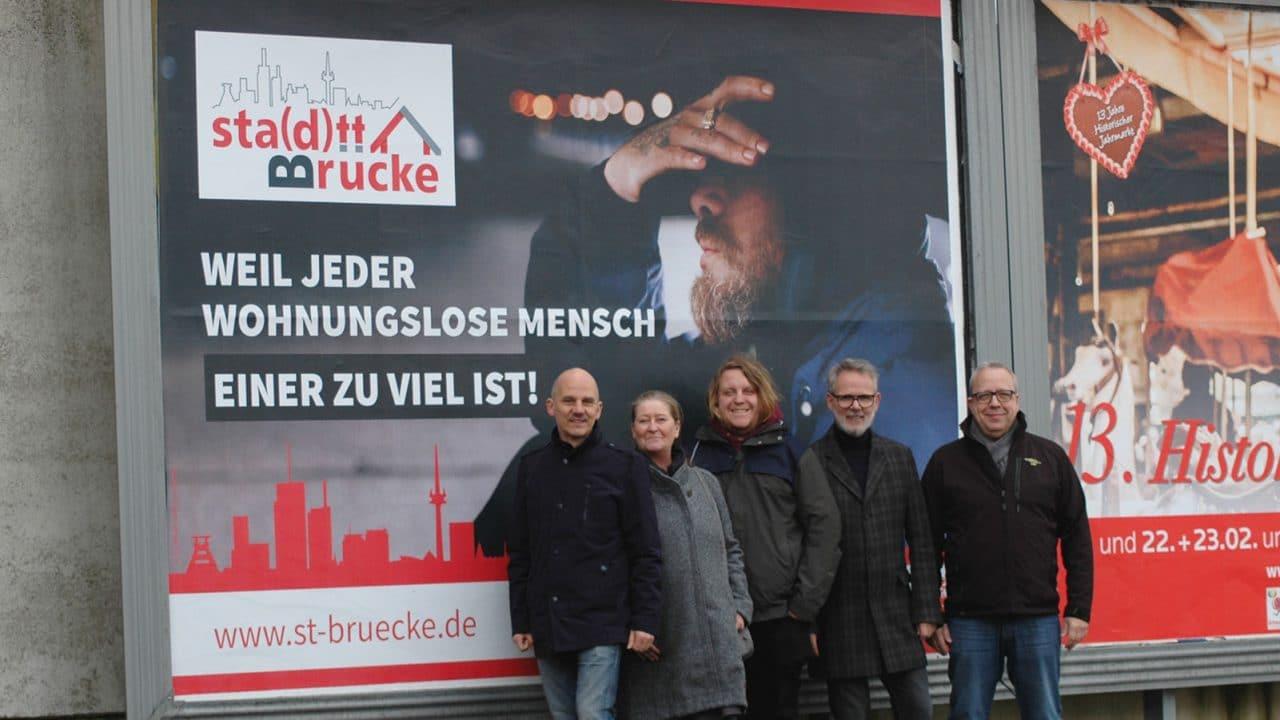 Foto: Gruppe Personen vor Plakat